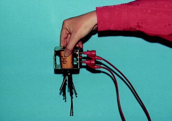 Eine stromdurchflossene Spule mit Eisenkern ist ein Elektromagnet: Sie zieht Körper aus ferromagnetischen Stoffen an.